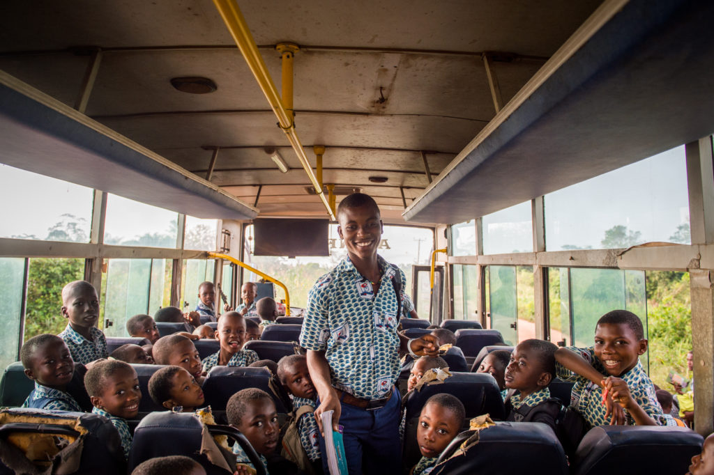 Baba boards a bus full of young students from the surrounding community.