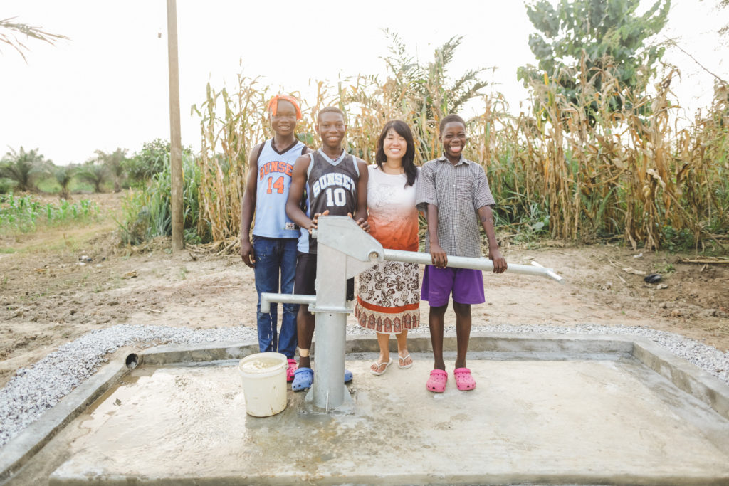 Shawna Sanches with Kofi, Felix, Godisking, and the new well . (Photo by NBarrett Photography.)