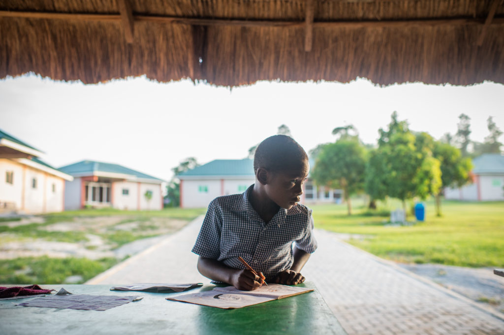 Esedem finishes a little homework before his school day begins.